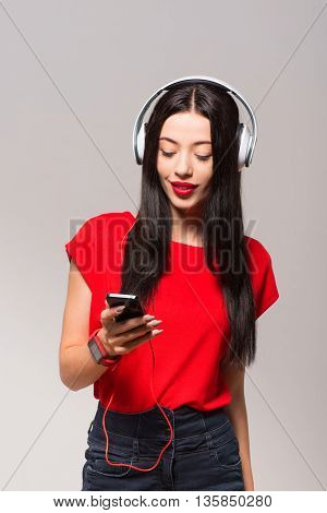 Feel the beat. Pleasant cheerful woman holding cell phone and listening to music while standing isolated on grey background