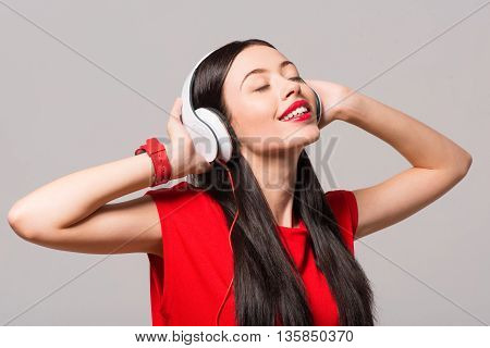 Enjoy the sounding. Positive delighted smiling woman closing her eyes and smiling while listening to music