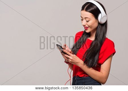 Time for rest. Pleasant delighted beautiful woman holding cell phone and listening to music while standing isolated on grey background
