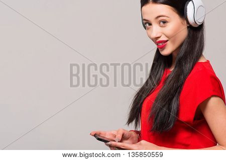 Mobile generation. Positive beautiful joyful woman holding cell phone and listening to music