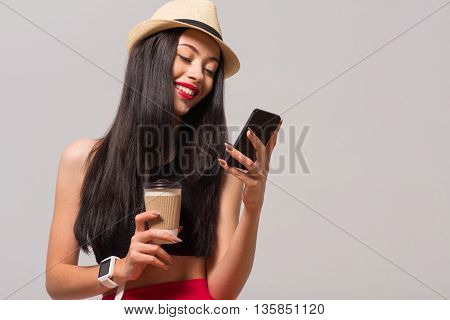 In connection. Positive charming smiling woman drinking coffee and holding cell phone while expressing joy