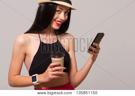 Share your emotions. Positive delighted woman holding cell phone and drinking coffee while expressing gladness