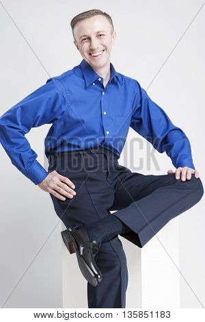 Happy Smiling Caucasian Man Sitting on White Box and Laughing. Posing Against White. Vertical Image Orientation