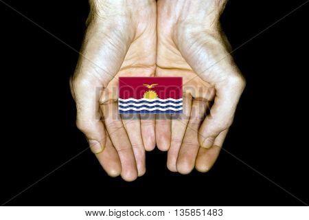 Flag Of Kiribati In Hands On Black Background