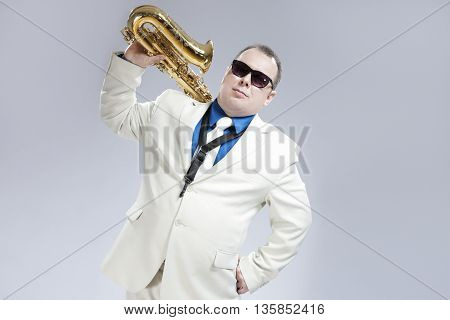 Portrait of Handsome Caucasian Saxophone Player With Music Instrument Over Shoulder. Posing Against White.Horizontal Image Orientation