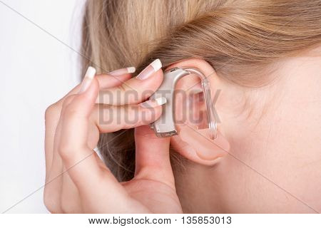 Close up of an ear of a girl with a hand inserting a hearing aid