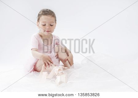 Portrait of Little Cute Caucasian Girl Posing as Ballerina and Wearing Toes. Against White. Horizontal Image Orientation