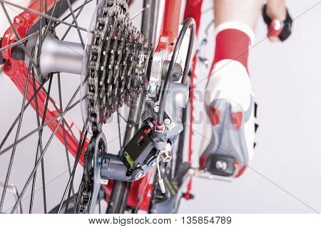 Cycling Ideas. Rear Derailleur and Cassette Sprokets Along With Cyclist Leg Closeup. Backside View. Horizontal Image