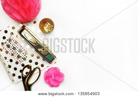 Flat lay gold stationery on white table notebook and stapler woman style desktop modern