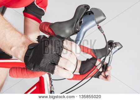 Road Cycling Sport Ideas and Concepts. Closeup of Athlete Hands in Gloves Holding Dual Controls Levers. Horizontal Image