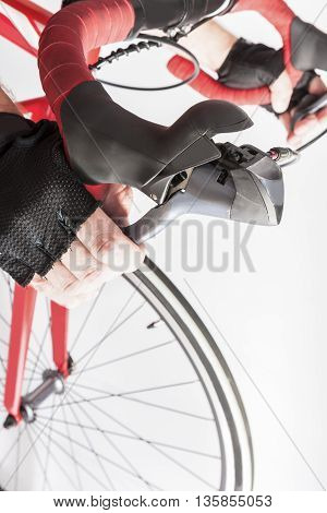Road Cycling Sport Ideas and Concepts. Closeup of Athlete Hands in Gloves Holding Dual Controls Levers. Vertical Image