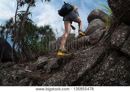 Woman hiker passing rocky terrain