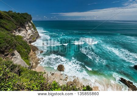 Indian ocean's coast with breaking waves and blue sky with some clouds. Bali, Indonesia