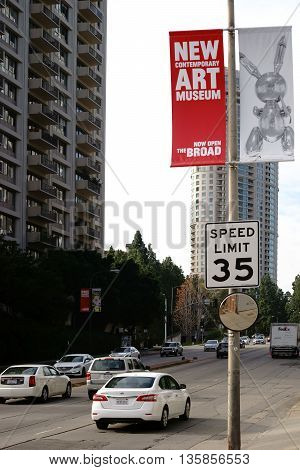 LOS ANGELES, UNITED STATES - DECEMBER 27: Traffic on a speed limit street in the center of Los Angeles with a sign from the Museum of Contemporary Art on December 27 2015 in Los Angeles.