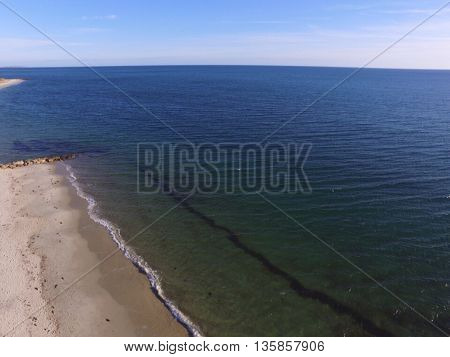 This is Nantucket Sound in December. With minimal boat traffic, the water is very clean. You can see the right through the water and the sand that lies below. The litter strip of seaweed shows where the water is during low tide and makes the picture look