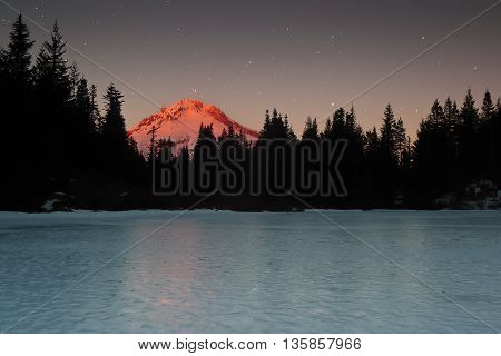 Sunset Illuminates Mount Hood And Mirror Lake Under a Starry Sky. Mt. Hood National Forest, Oregon.