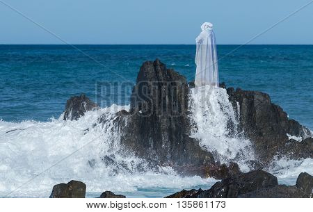 Spirit image of Jesus Christ standing on some coastal rocks with white sea waves splashing over the rocks.