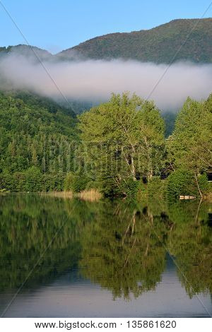Morning at Pliva Lake with white cloud hanging in the middle of air Jajce Bosnia and Herzegovina