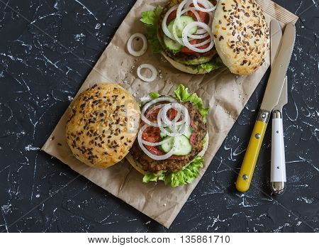 Healthy vegetarian zucchini burgers on dark stone background.