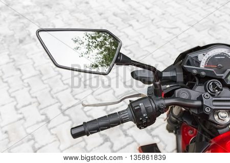 Motorcycle rear view mirror and reflection of blue sky and tree.