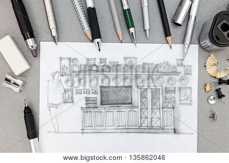 Designer Workplace With Freehand Sketch Of Wall Unit And Various Drawing Tools