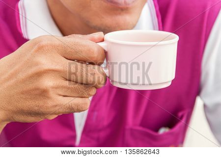 Young man holding a cup of coffee in  the cafe and soft-focus background,select focus front hand.