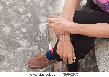 man smoking a cigarette, a hand of the man holding cigarette while sitting,select focus front hand and soft-focus background.