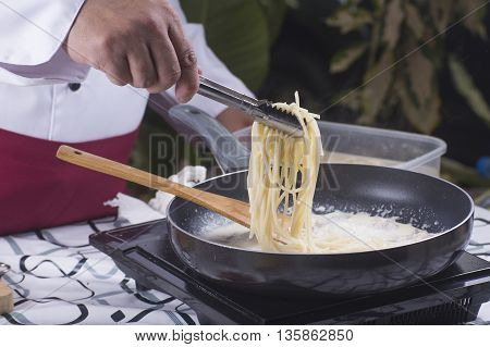 Spaghetti lifted on the pan with tongs / cooking spaghetti concept