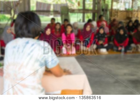 Blurred abstract background of university students sitting in a lecture room with teacher of the out Community education: Blurry view from back of the classroom: Teachers day