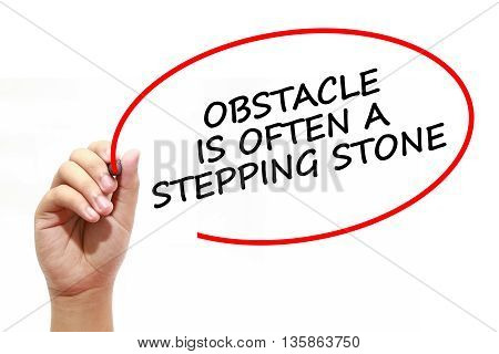 Man writing OBSTACLE IS OFTEN A STEPPING STONE with marker on transparent wipe board.