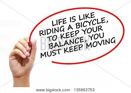 Man writing LIFE IS LIKE RIDING A BICYCLETO KEEP YOUR BALANCEYOU MUST KEEP MOVING with marker on transparent wipe board.