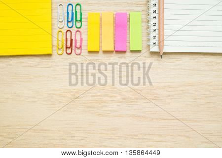 Top view of stationery items - notepad notebook sticky note paper clips pencil - on wooden background - desk above flat lay items on wooden table