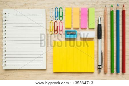 Colorful set of stationery notepad paper clips sticky notes pen pencil colored pencils on wooden background - concept of back to school