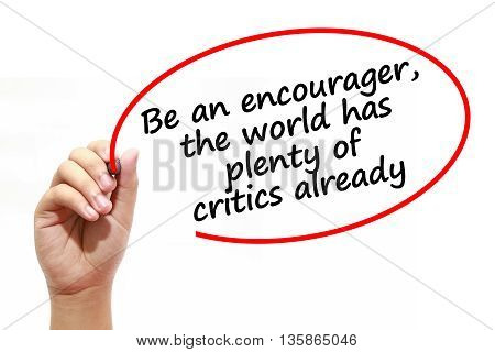 Man writing Be an encouragerthe world has plenty of critics already with marker on transparent wipe board.
