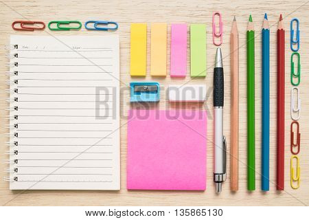 Top view flat lay of colorful set of stationery tool and equipment - notepad paper clips sticky notes pen pencil colored pencils eraser shapener - on wooden background - concept of back to school
