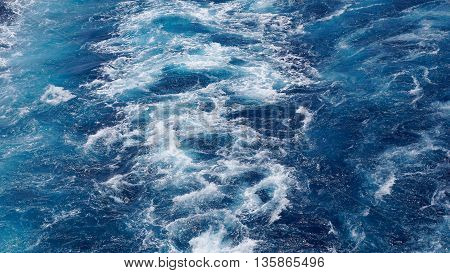 The foam on the blue water of sea