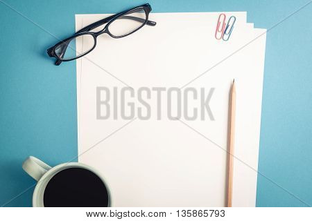 Desk above top view of an empty white plain paper with brown pencil paper clips black glasses and a glass of coffee on pastel blue background