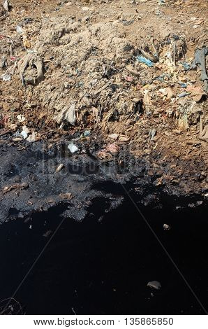 BALI INDONESIA - APRIL 30: Toxic household garbage plastic bags and hazardous industrial waste contaminates land and water at a polluted landfill site on April 30 2016 in Bali Indonesia.