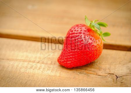 Focus placed fresh strawberries on a wooden floor.