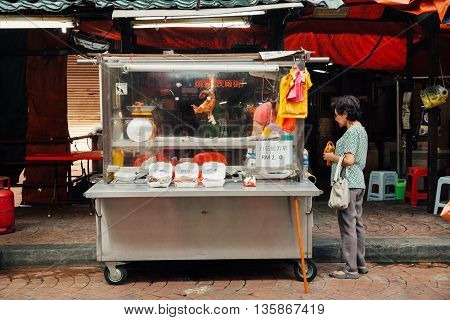 KUALA LUMPUR MALAYSIA - MARCH 17: Woman buying meat at the street stall in Chinatown Kuala Lumpur Malaysia on March 17 2016.