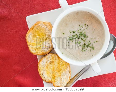 Top view of mushroom soup and baked bread on white soup bowl on a red placemat