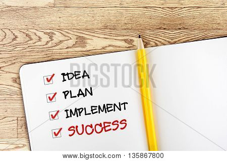 Open blank notebook with yellow pencil and success check box on wooden tablebusiness concept.
