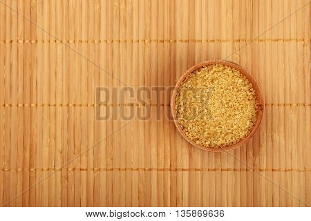 Wooden Bowl Of Brown Cane Sugar On Bamboo Mat