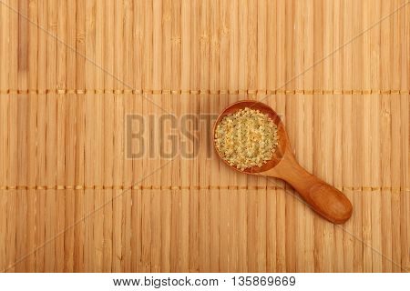 Scoop Of Brown Cane Sugar On Bamboo Mat