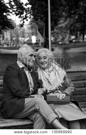 Walk. Elderly couple talking on a park bench. Black and white. True love.