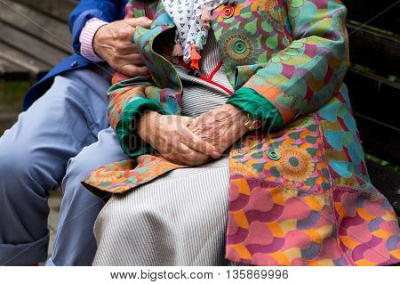 Elderly couple sitting on a bench outdoors. Hands close-up. True love.