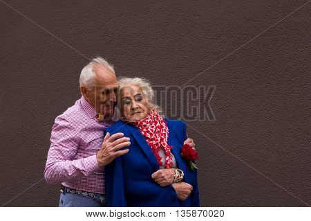 An old man gently embraces the elderly woman. True love.