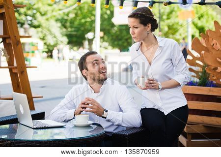 Business Team man and woman at Cafe having a conversation using laptop. Working Meeting Concept.
