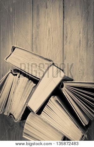 Stack Of Old And Used Hardback Books Or Text Books On Wooden Background. Monochrome