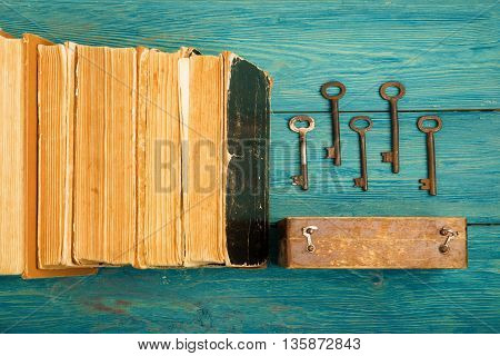 Old Keys And Stack Of Antique Books On Blue Wooden Background